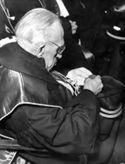 [Il professore Alessandro Lanfranchi guarda il Sigillum Magnum che gli è stato consegnato per il suo collocamento a riposo: inaugurazione dell'anno accademico 1952-53 e commemorazione di Vittorio Emanuele Orlando: aula magna dell'università di Bologna: 15 gennaio 1953]