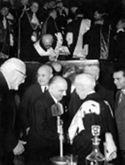 [Il professore Alfredo Galletti riceve le congratulazioni del prefetto Aurelio Gaipa per l'orazione inaugurale delle celebrazioni carducciane nel cinquantenario della morte del poeta: aula magna dell'università di Bologna: 16 febbraio 1957]